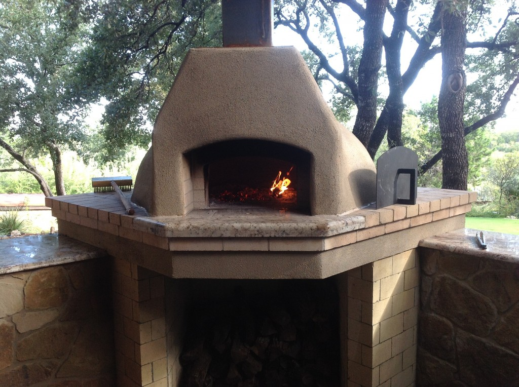 Wood-burning pizza oven with small wood curing fire.