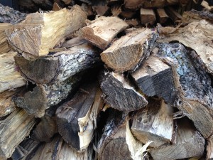double-split seasoned oak is ready stacked and ready to burn in a wood-fired pizza oven. Seasoned wood burns cleanly and efficiently.