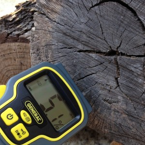 Moisture meter checking hardwood for moisture. Seasoned wood should read less than 20% moisture and will burn cleanly with less smoke.