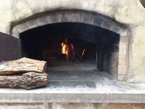 How to add wood to a pizza oven or wood-burning oven by Texas Oven Co. Start with a small fire.