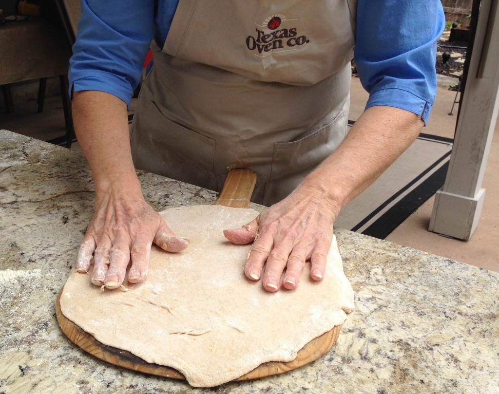 Foolproof-Pizza dough shaped on pizza peel for wood-fired oven pizza oven.
