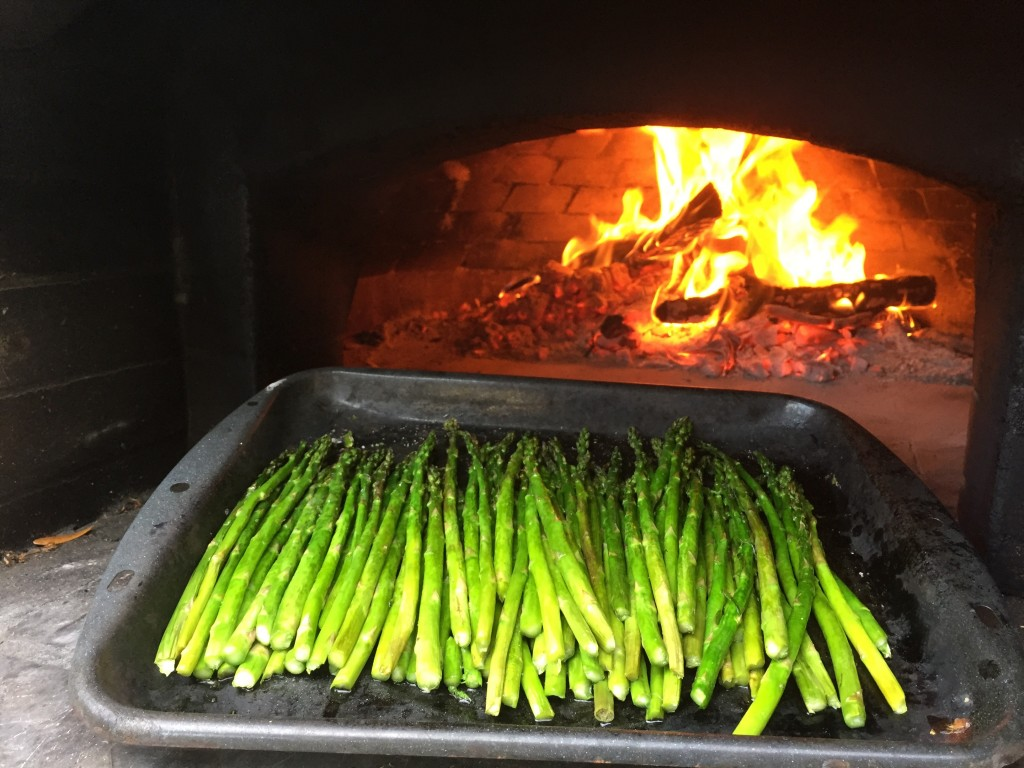 wood-fired asparagus roasting in wood-burning oven